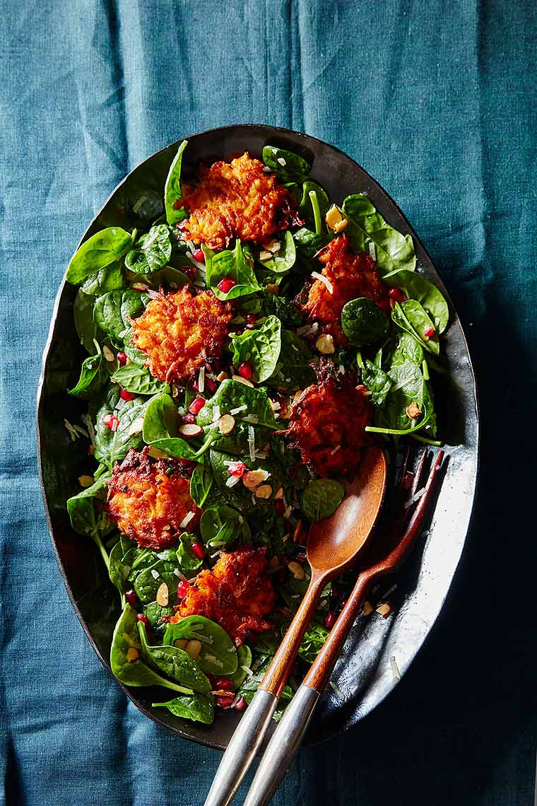 sweet potato fritter and spinach salad with pomegranate arils, spinach